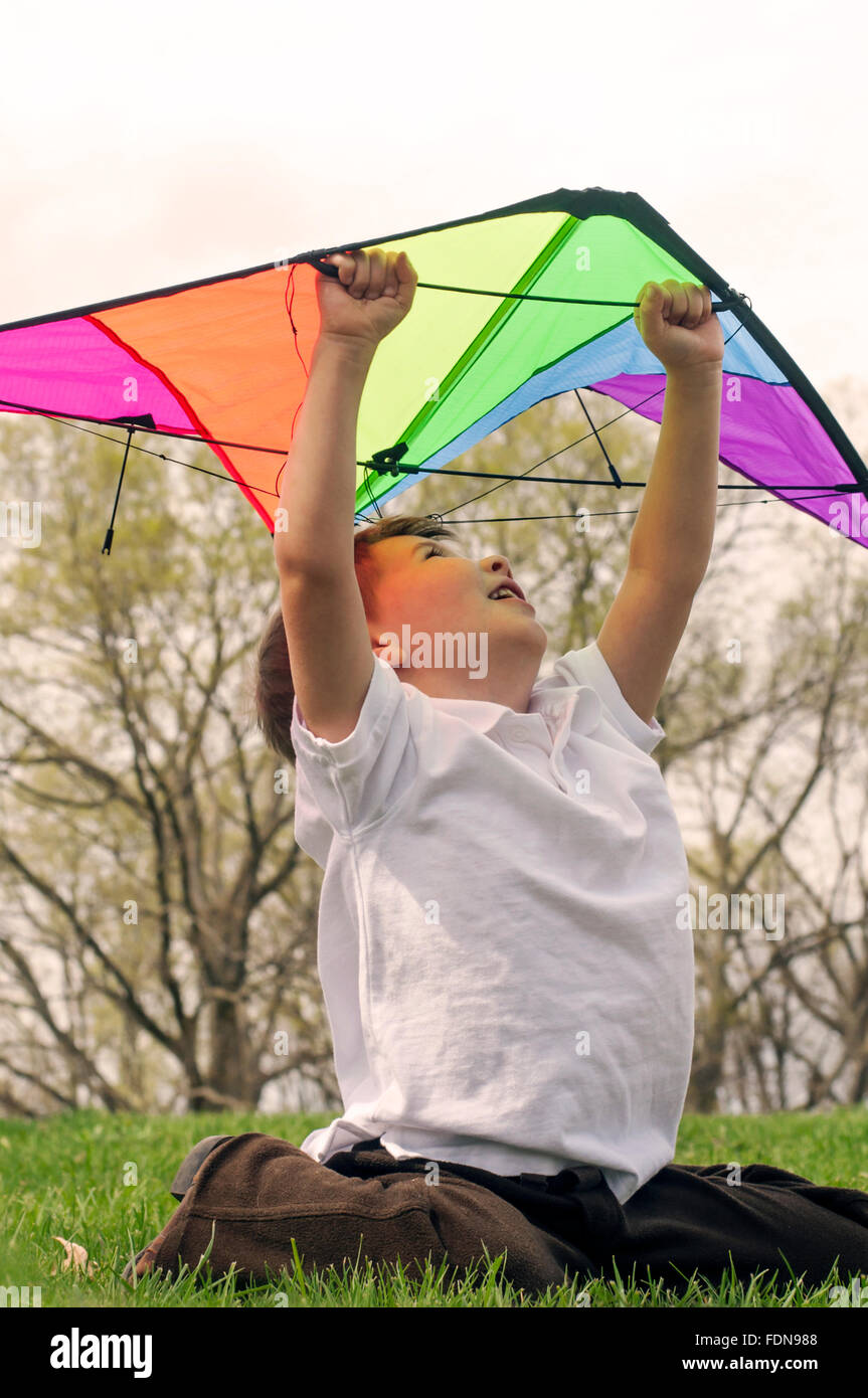 Boy looking up holding kite - Stock Image