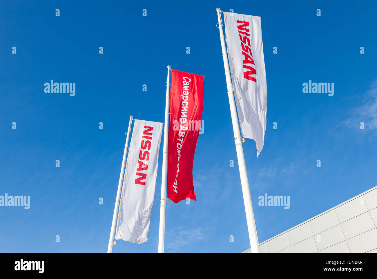 The flags of official dealer Nissan over blue sky Stock Photo