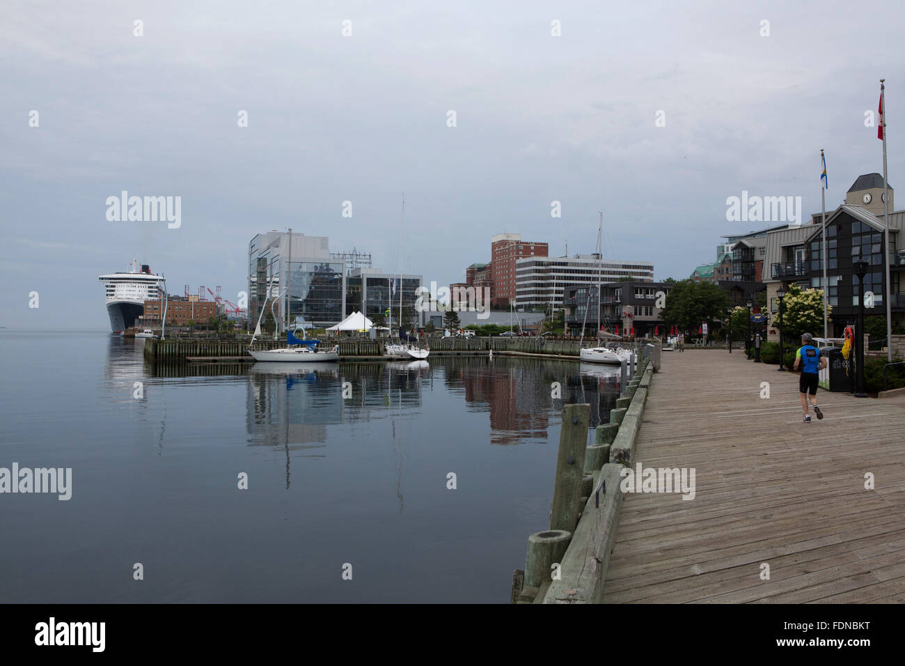 A man jogs on the wooden wharves by the waterfront in Halifax, Canada. The wharves are a legacy of the freight trade - Stock Image
