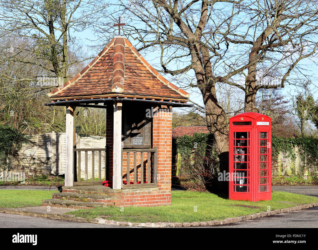 English Village War Memorial shelter and red telephone box - Stock Image