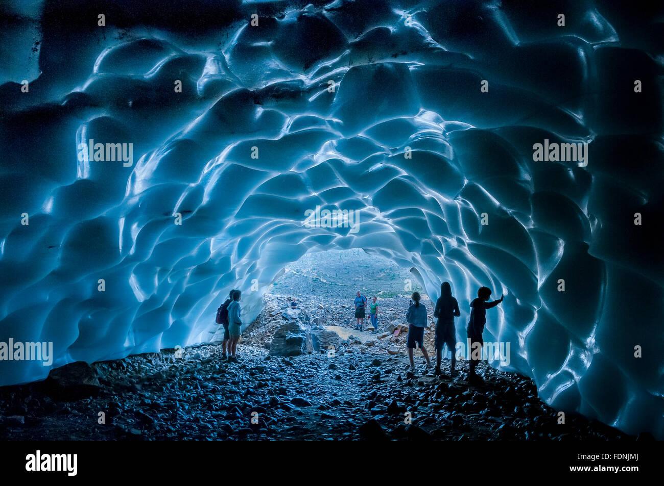 People explore ice cave in Cavell Glacier, Jasper National Park, Alberta, Canada - Stock Image