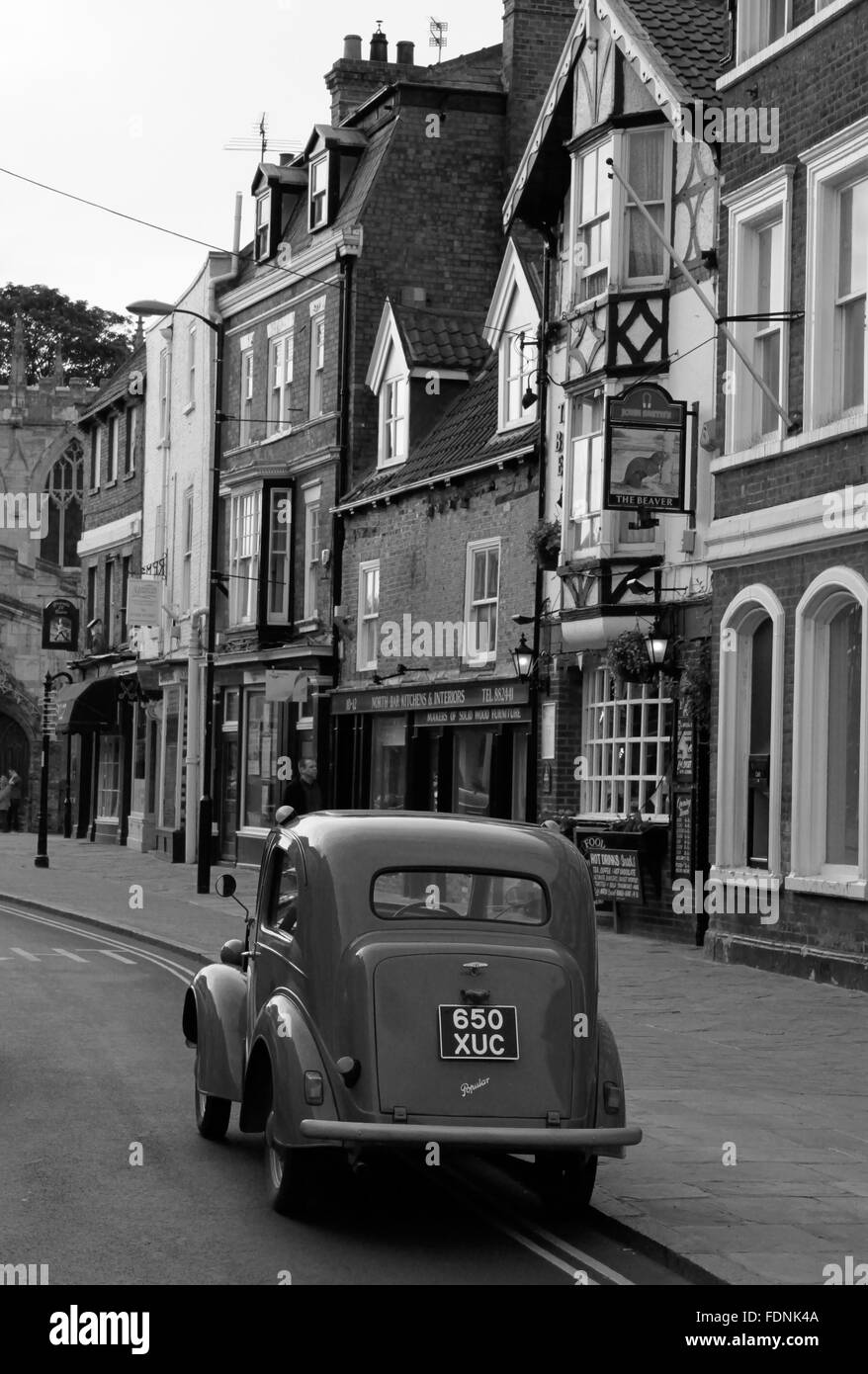 black and white 1950s Ford popular parked outside old pub in Beverley, Yorks Stock Photo