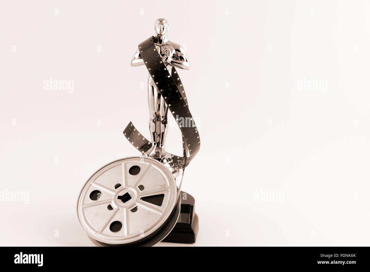 Academy Award Oscar statue with vintage movie reel desaturated with sepia tones. - Stock Image