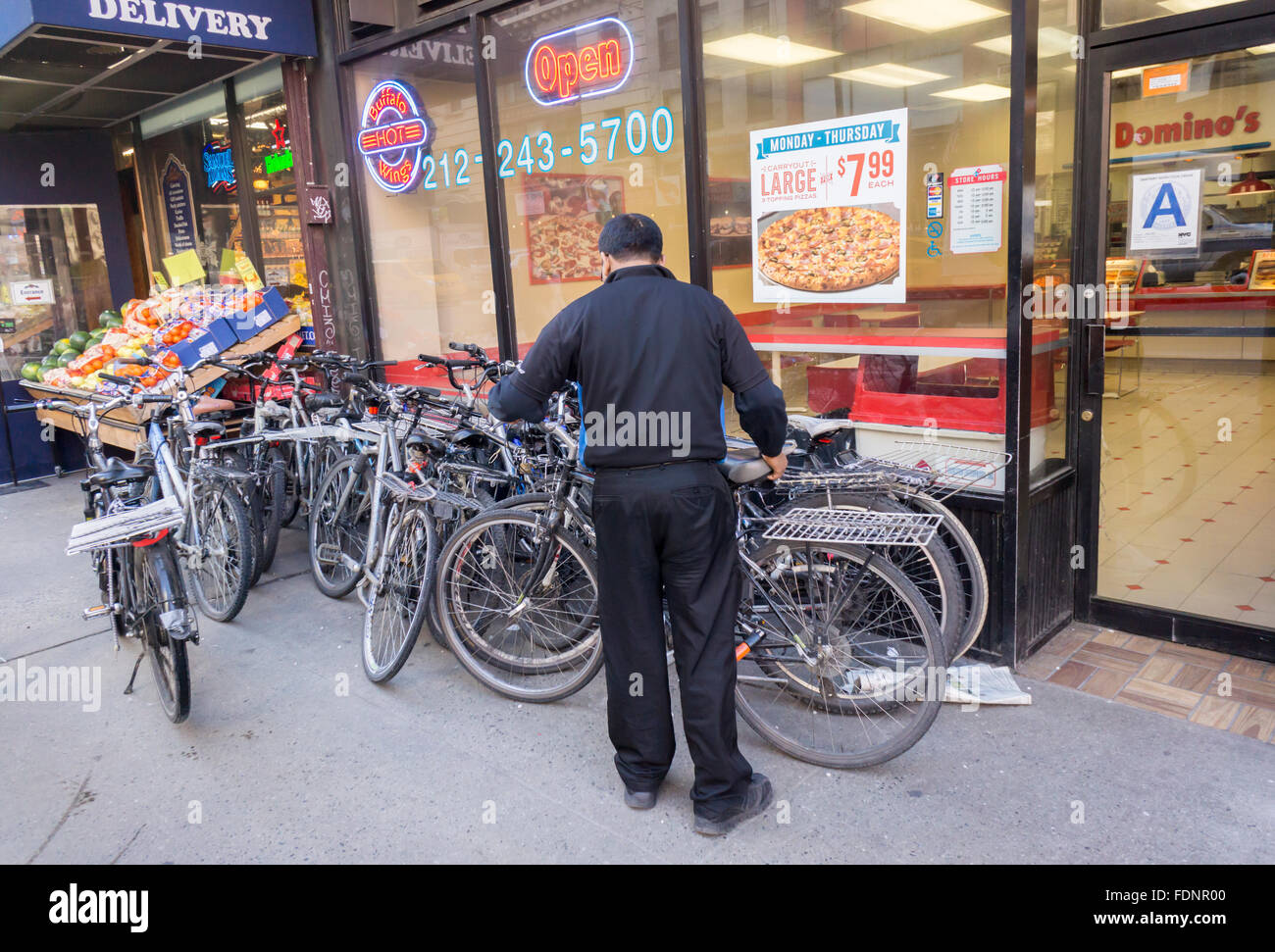 A worker at a Domino's Pizza in New York arranges their collection of delivery bicycles outside of the store - Stock Image