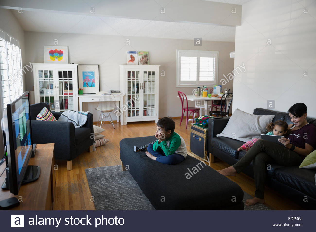Mother and children relaxing watching TV living room - Stock Image