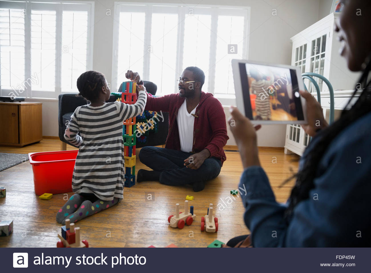 Mother photographing family stacking blocks - Stock Image