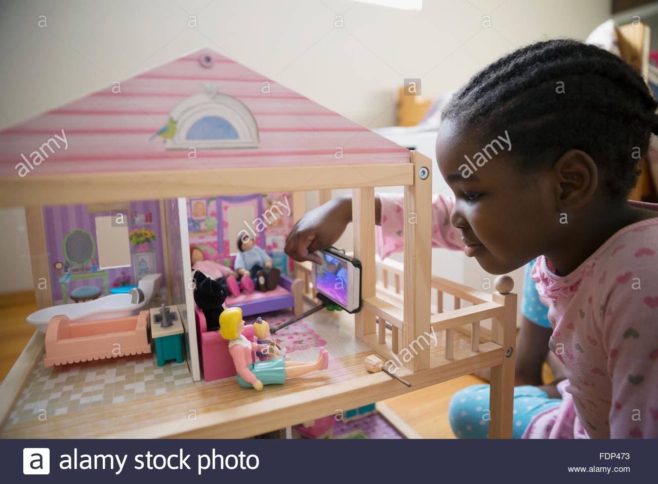 Girl photographing dolls in dollhouse - Stock Image
