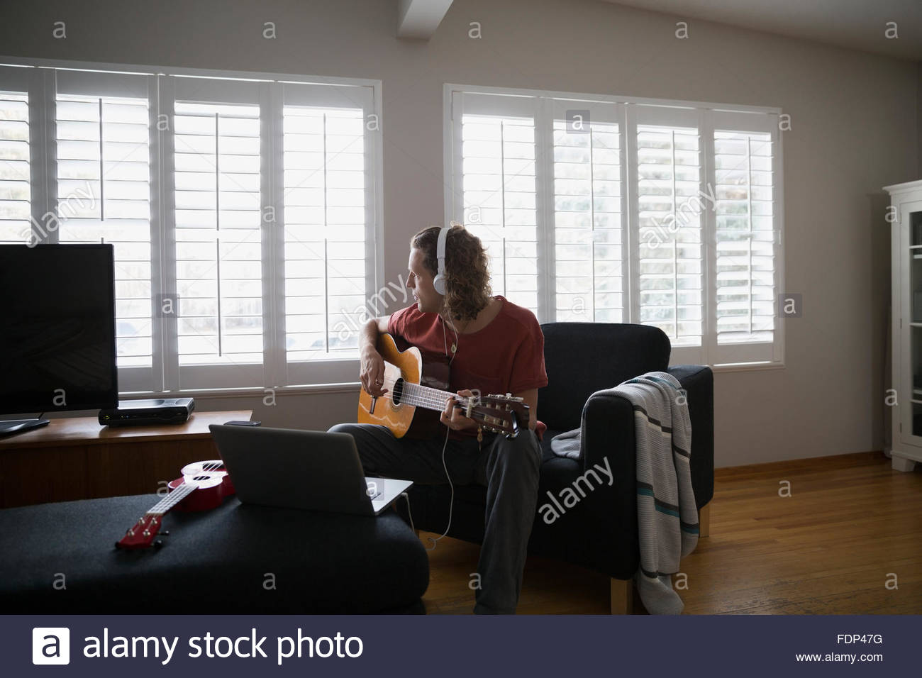 Man with headphones playing guitar in living room - Stock Image