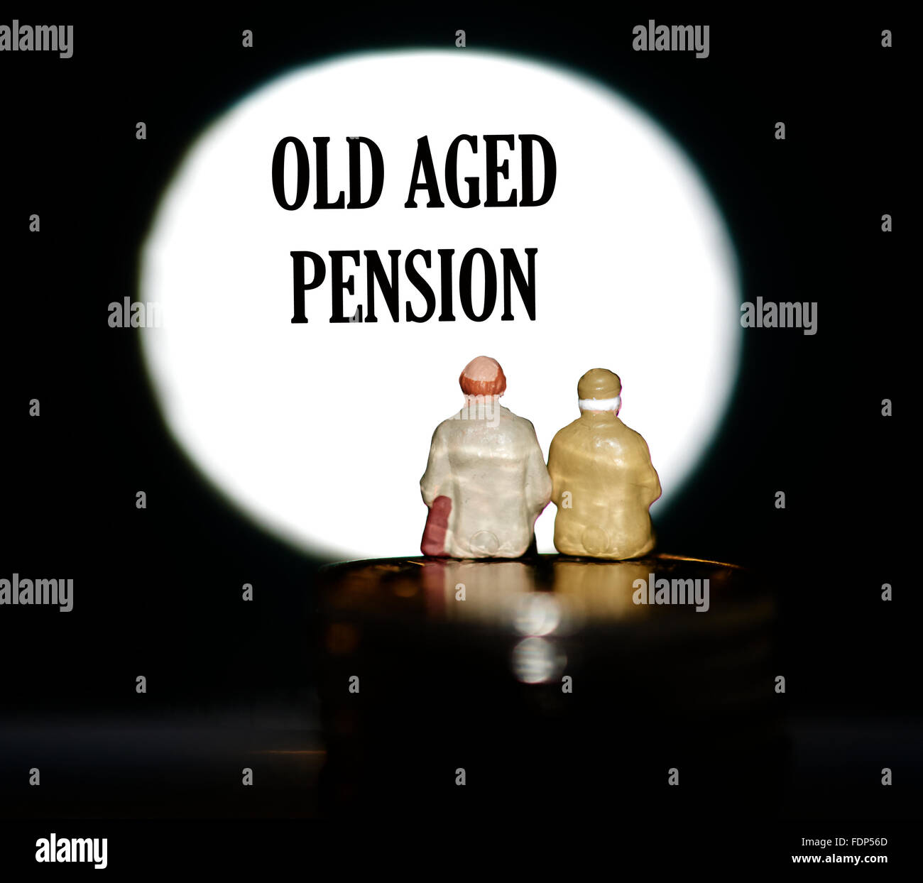 Miniature figurine pensioners sitting on coins in front of a spotlight showing the words Old age pension concept Stock Photo