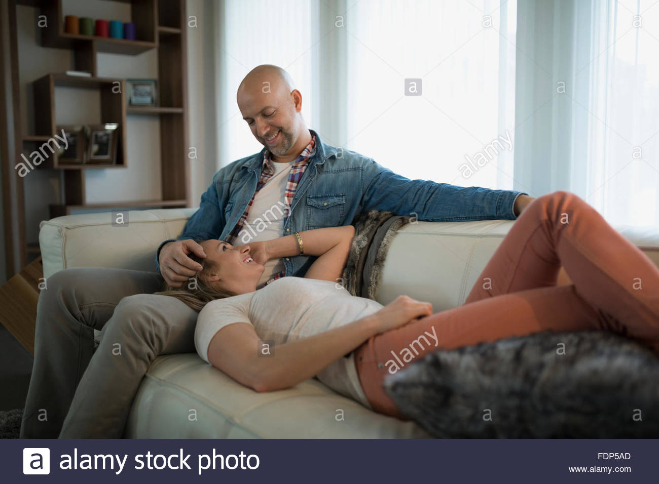 woman laying on husbands lap living room sofa - Stock Image
