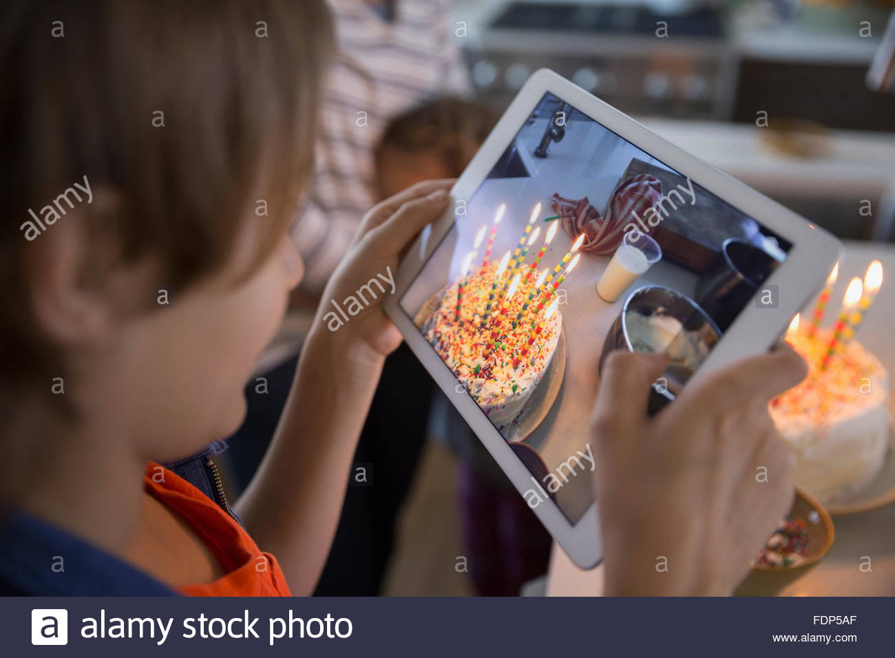 Boy photographing birthday cake with candles - Stock Image