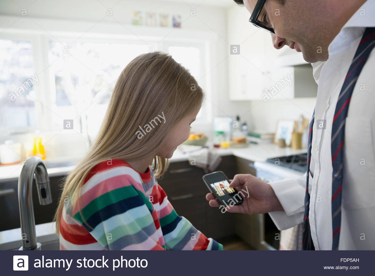 Father and daughter using cell phone in kitchen - Stock Image
