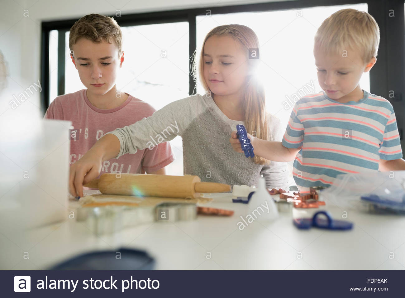 Brothers and sister baking cookies - Stock Image