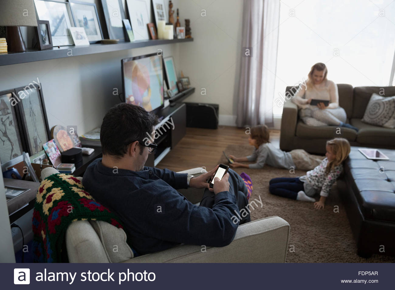 Family relaxing in living room with digital technology - Stock Image