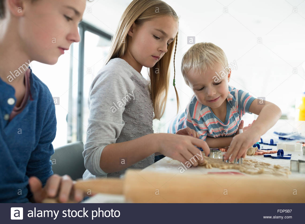 Brothers and sister baking with cookie cutters - Stock Image