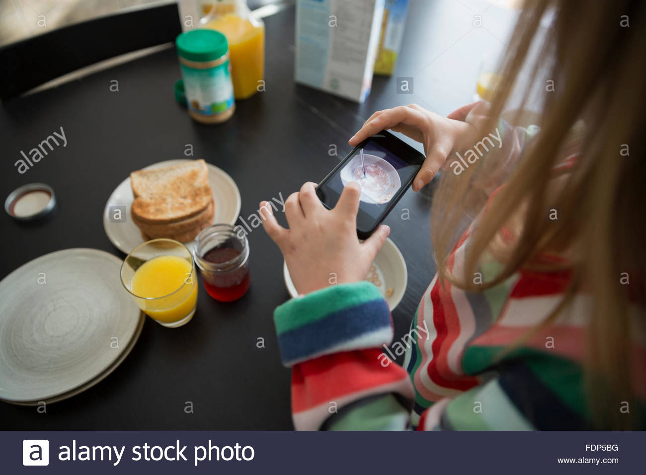 Girl photographing breakfast with camera phone - Stock Image