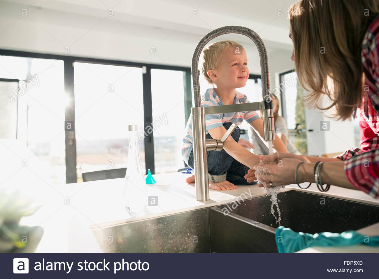 mother washing hands in kitchen sink - Stock Image