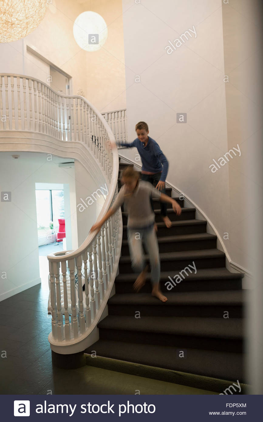Brother chasing sister down foyer staircase - Stock Image