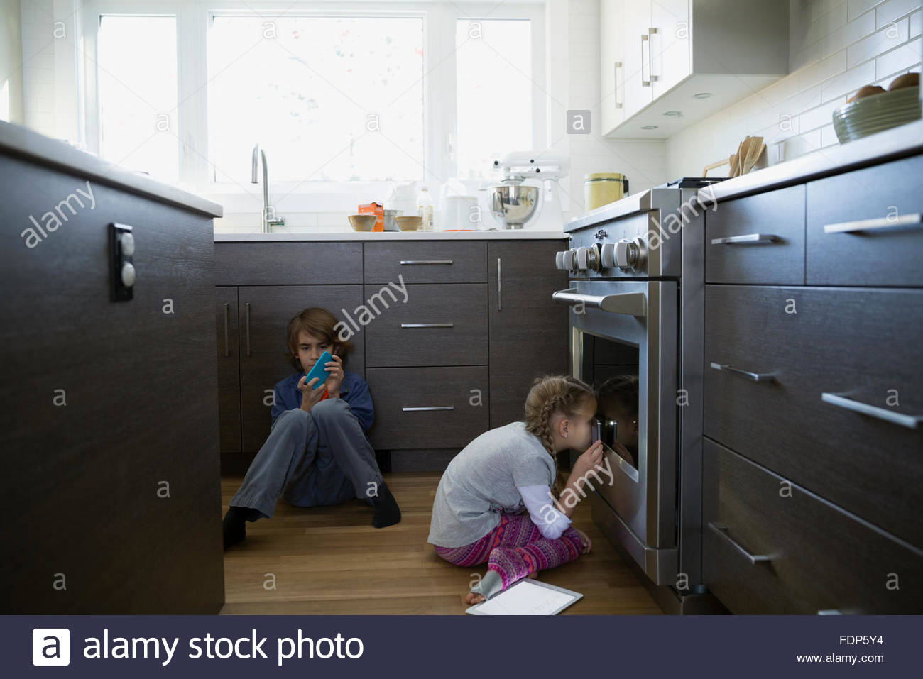 Girl peering into oven in kitchen - Stock Image