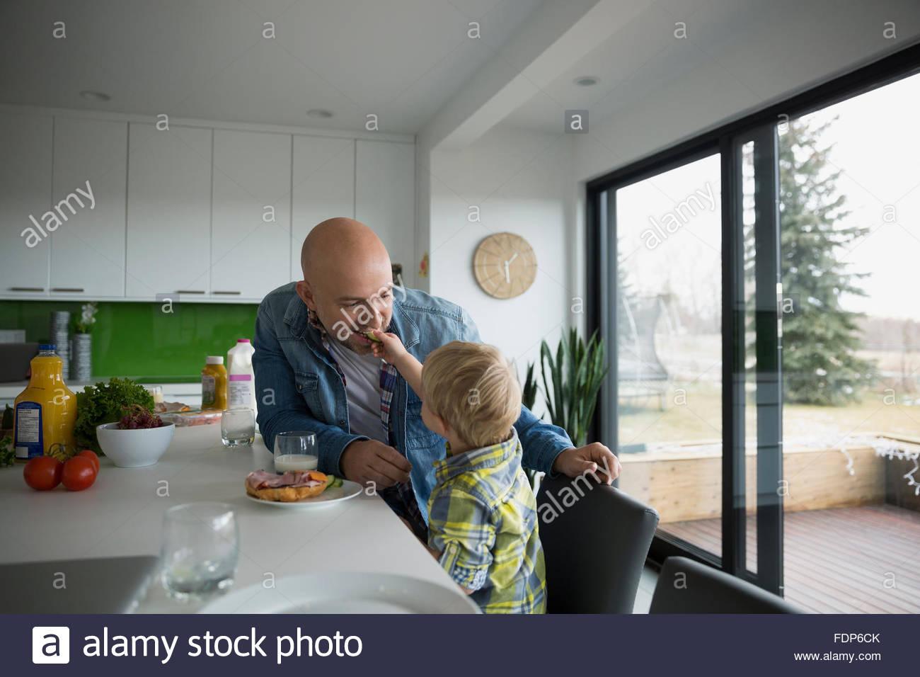 Boy feeding father at kitchen island - Stock Image