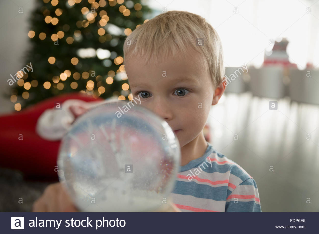 Wide-eyed boy looking at snow globe - Stock Image