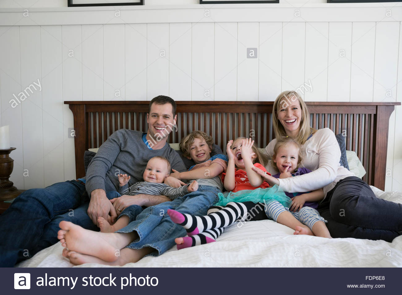 Portrait laughing family relaxing on bed - Stock Image