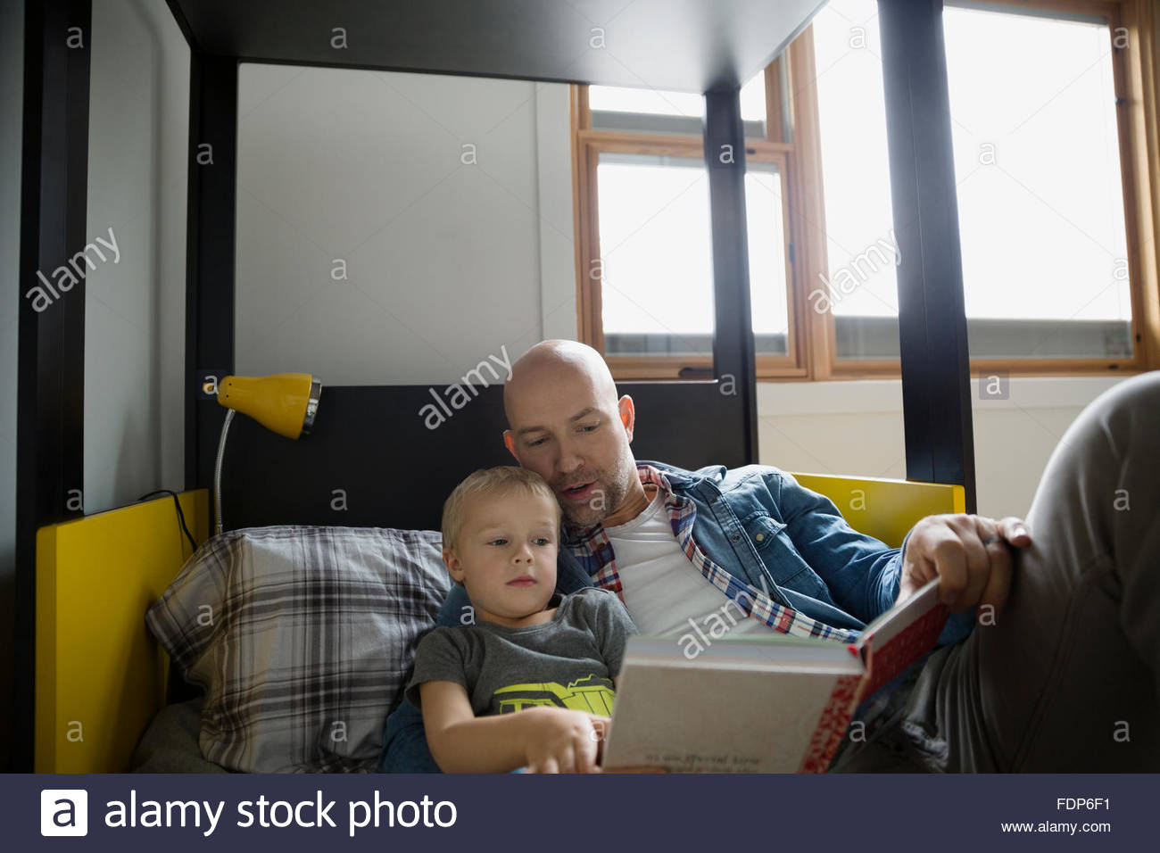 Father and son reading book on bed - Stock Image