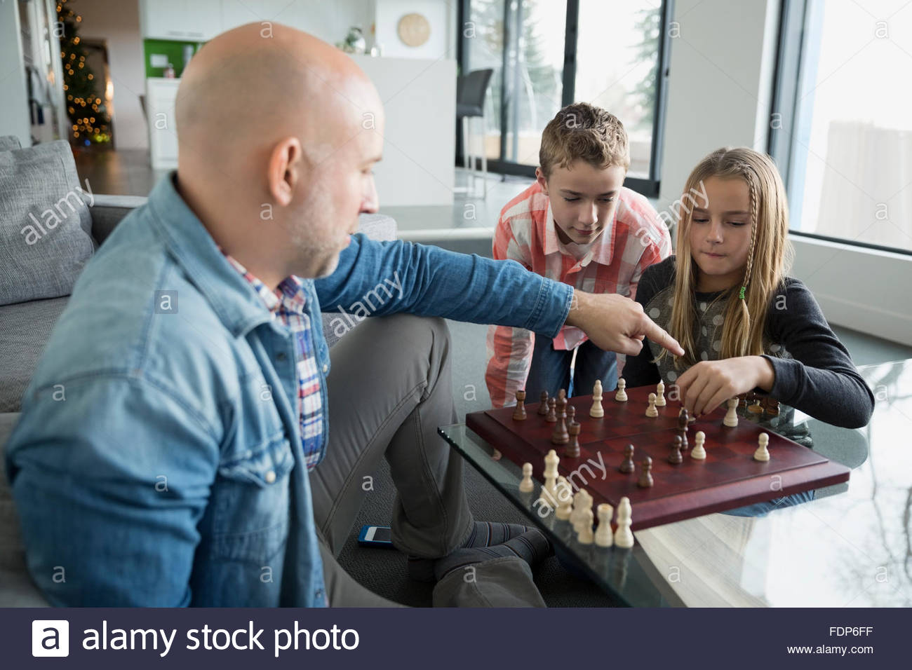 Father and children playing chess - Stock Image
