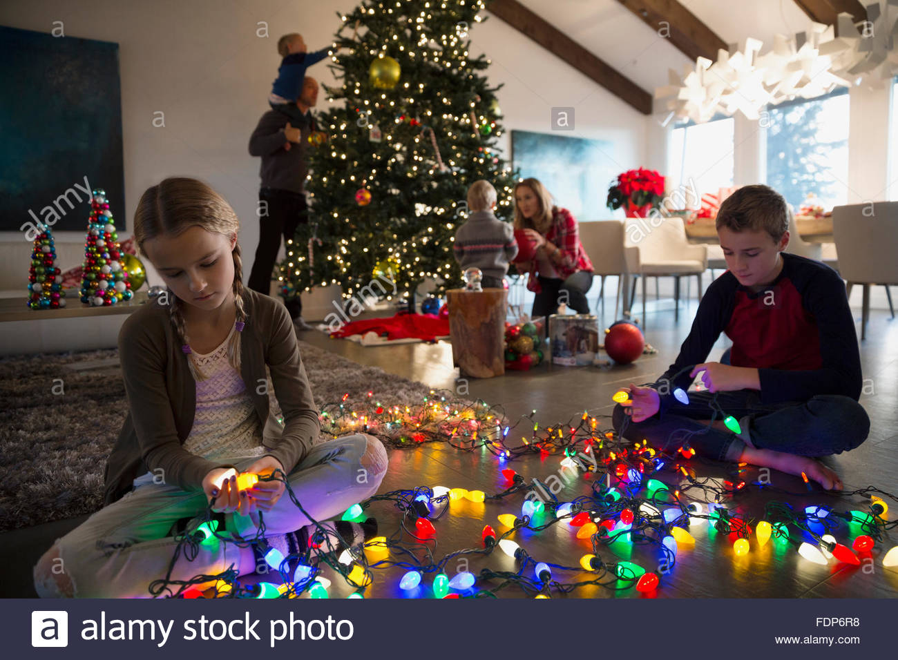 Brother and sister untangling Christmas tree string lights - Stock Image