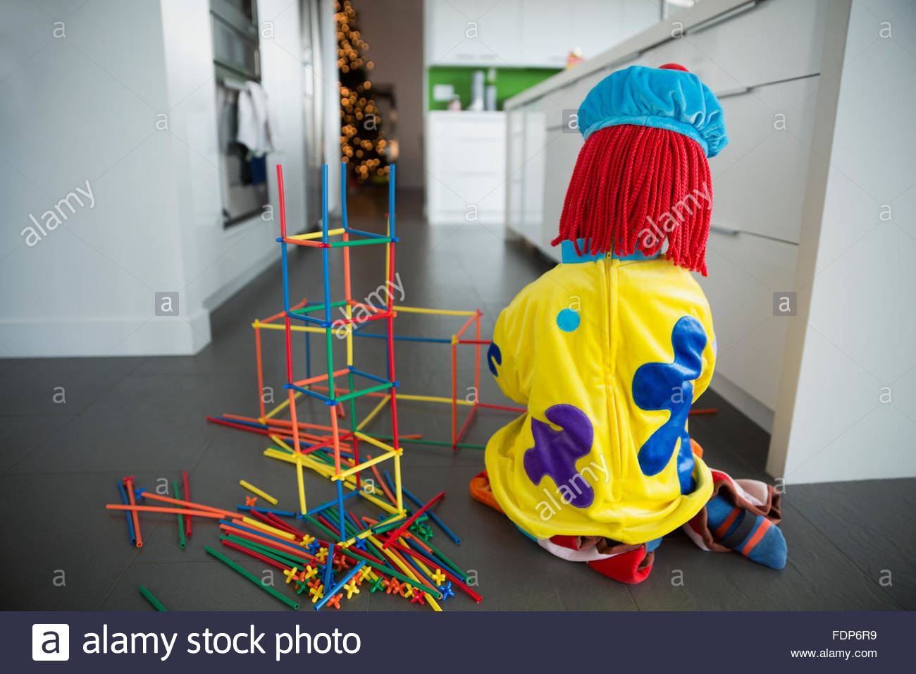 Boy in clown costume playing with connector sticks - Stock Image