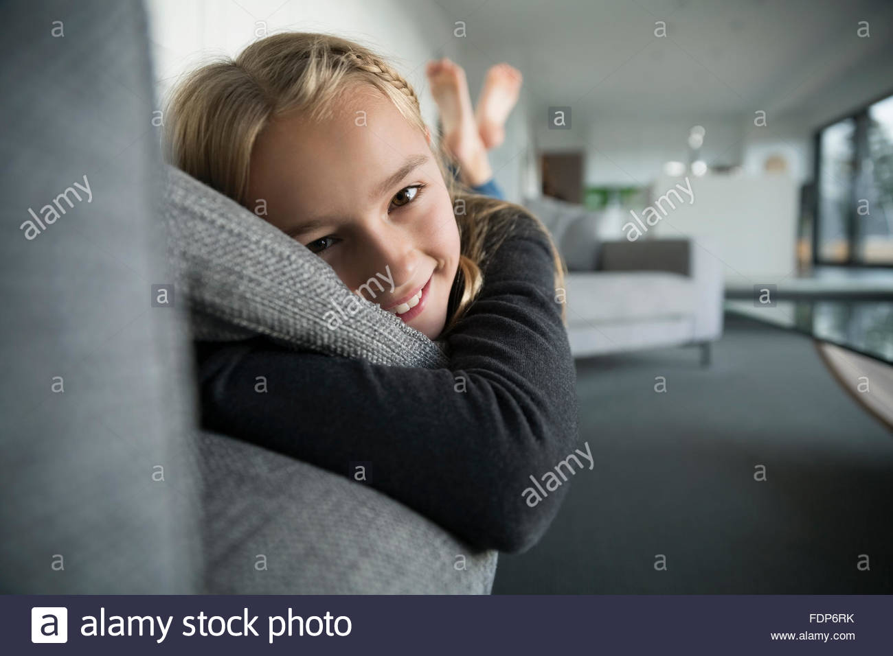 Portrait smiling girl laying on sofa - Stock Image