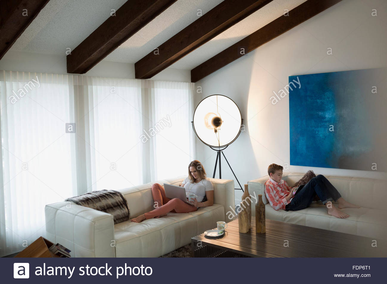 Mother and son using laptop digital tablet sofas - Stock Image