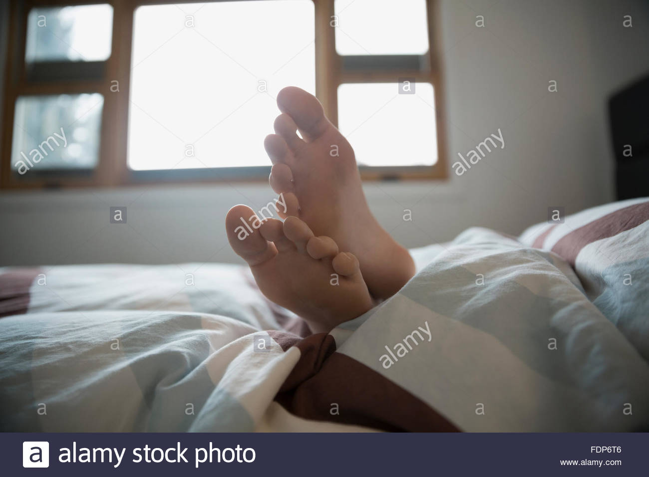 close up girls bare foot on bed - Stock Image