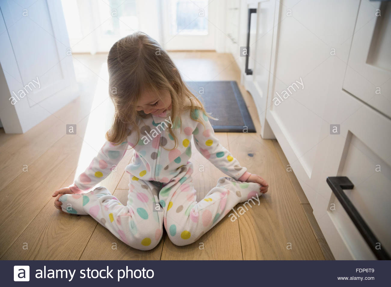 Cute girl polka-dot pajamas sitting kitchen floor - Stock Image