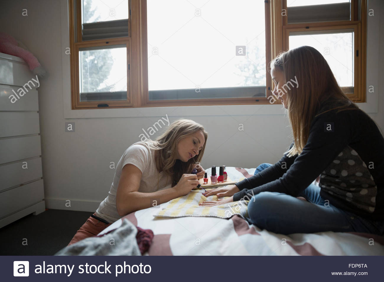 mother painting daughters fingernails on bed - Stock Image