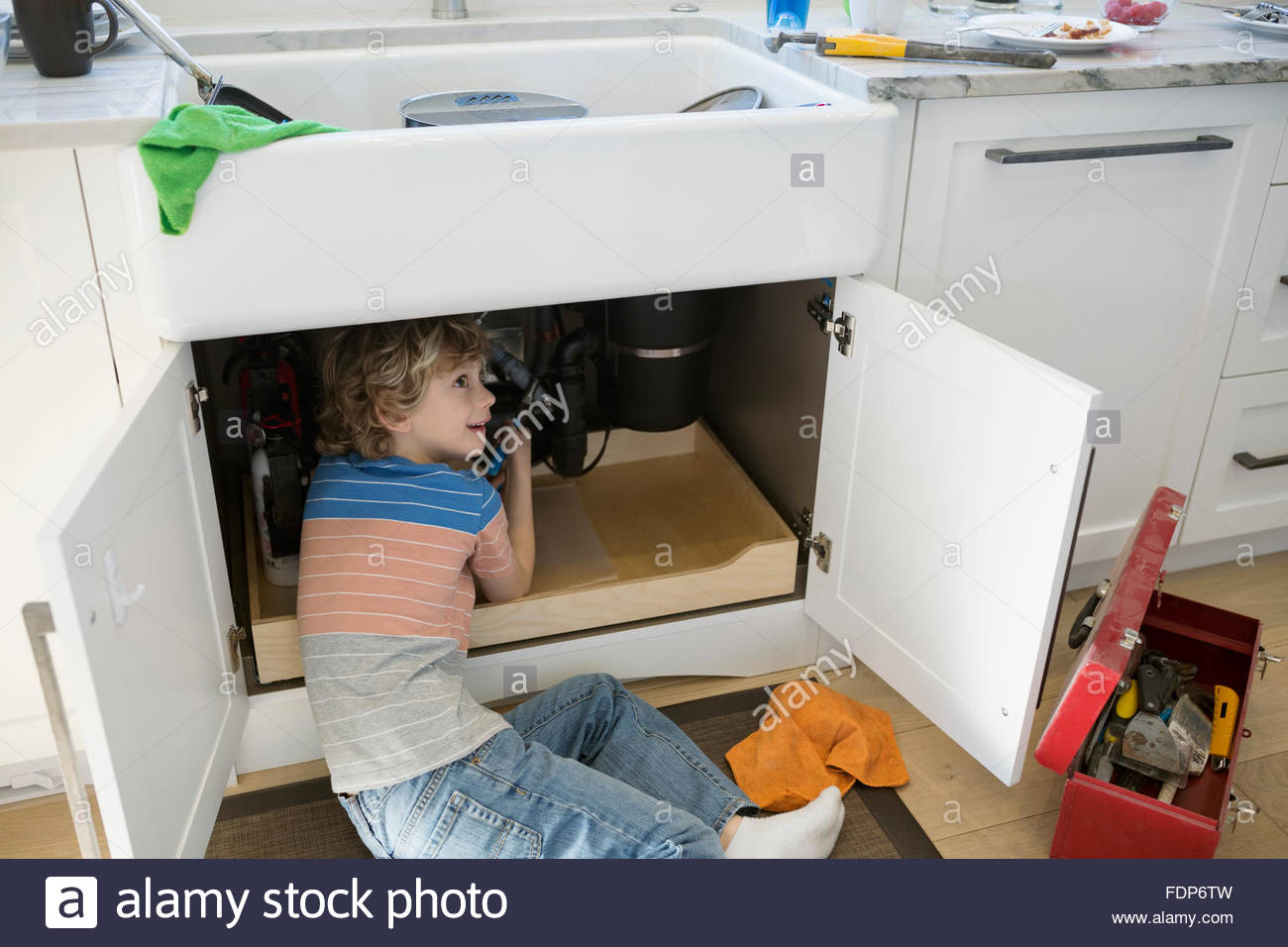 Boy trying to fix pipe under kitchen sink - Stock Image