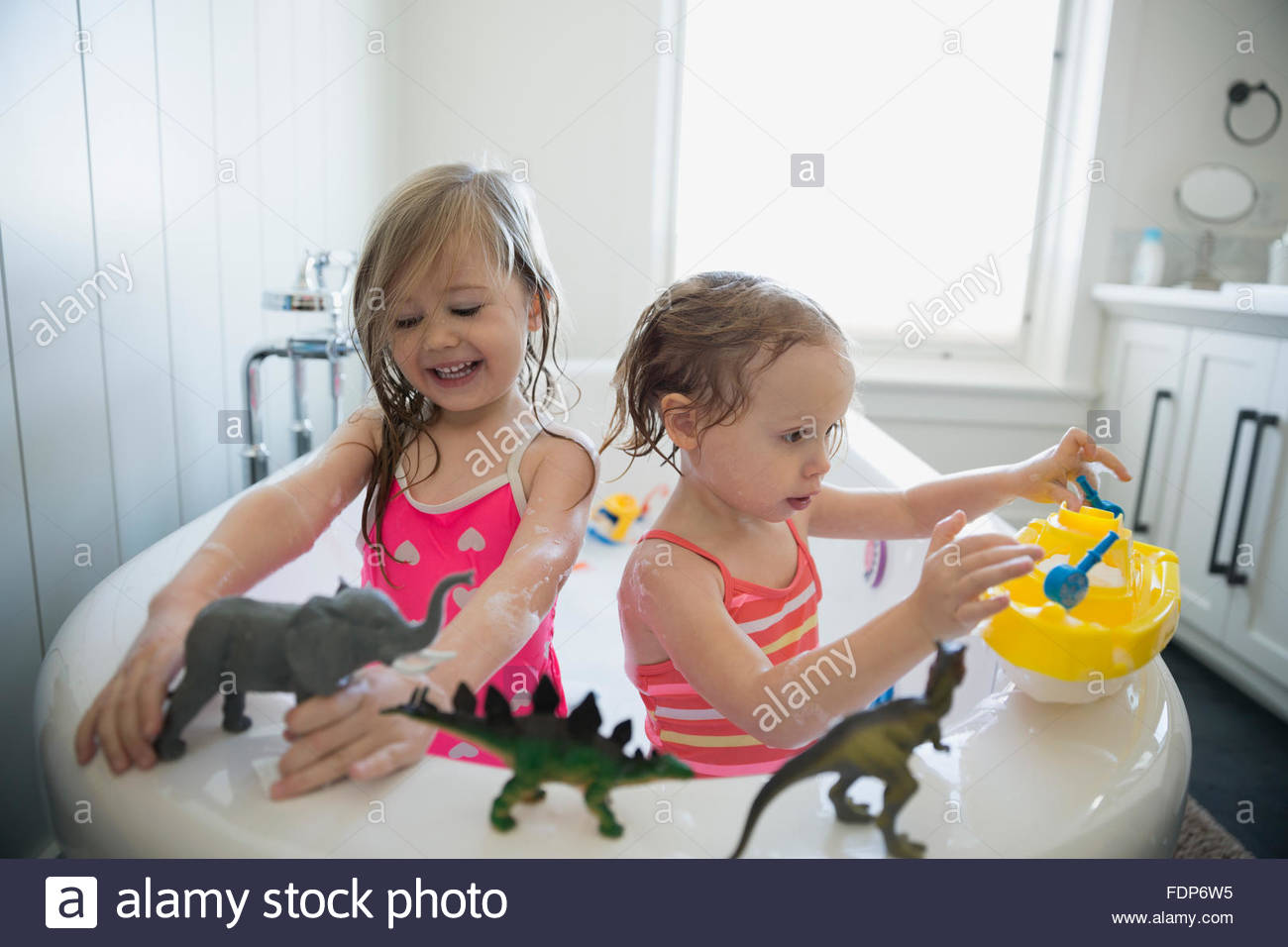 Sisters playing with toy animals in bath - Stock Image