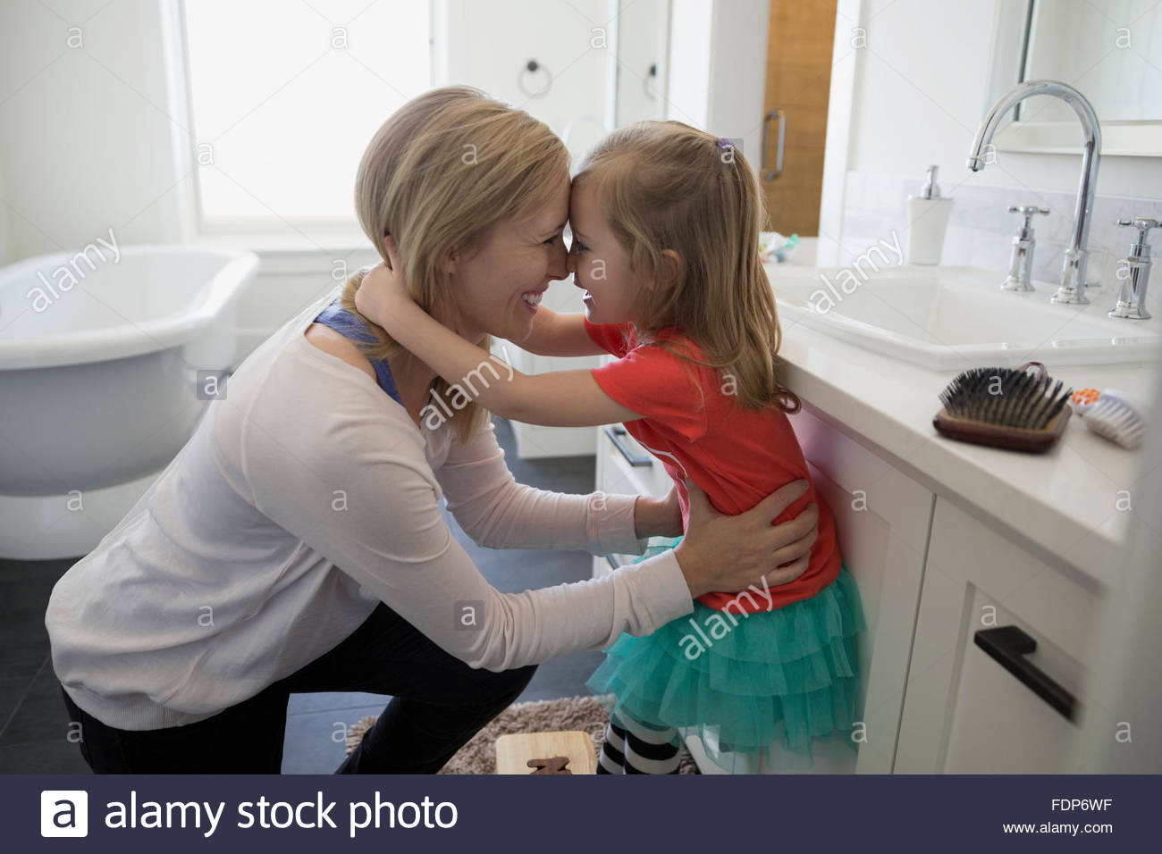 Affectionate mother and daughter rubbing noses in bathroom - Stock Image