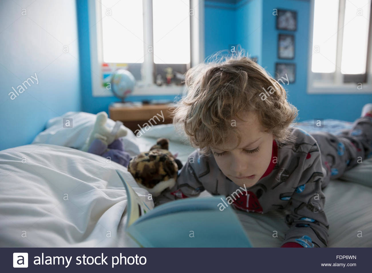 Boy in pajamas reading book on bed - Stock Image