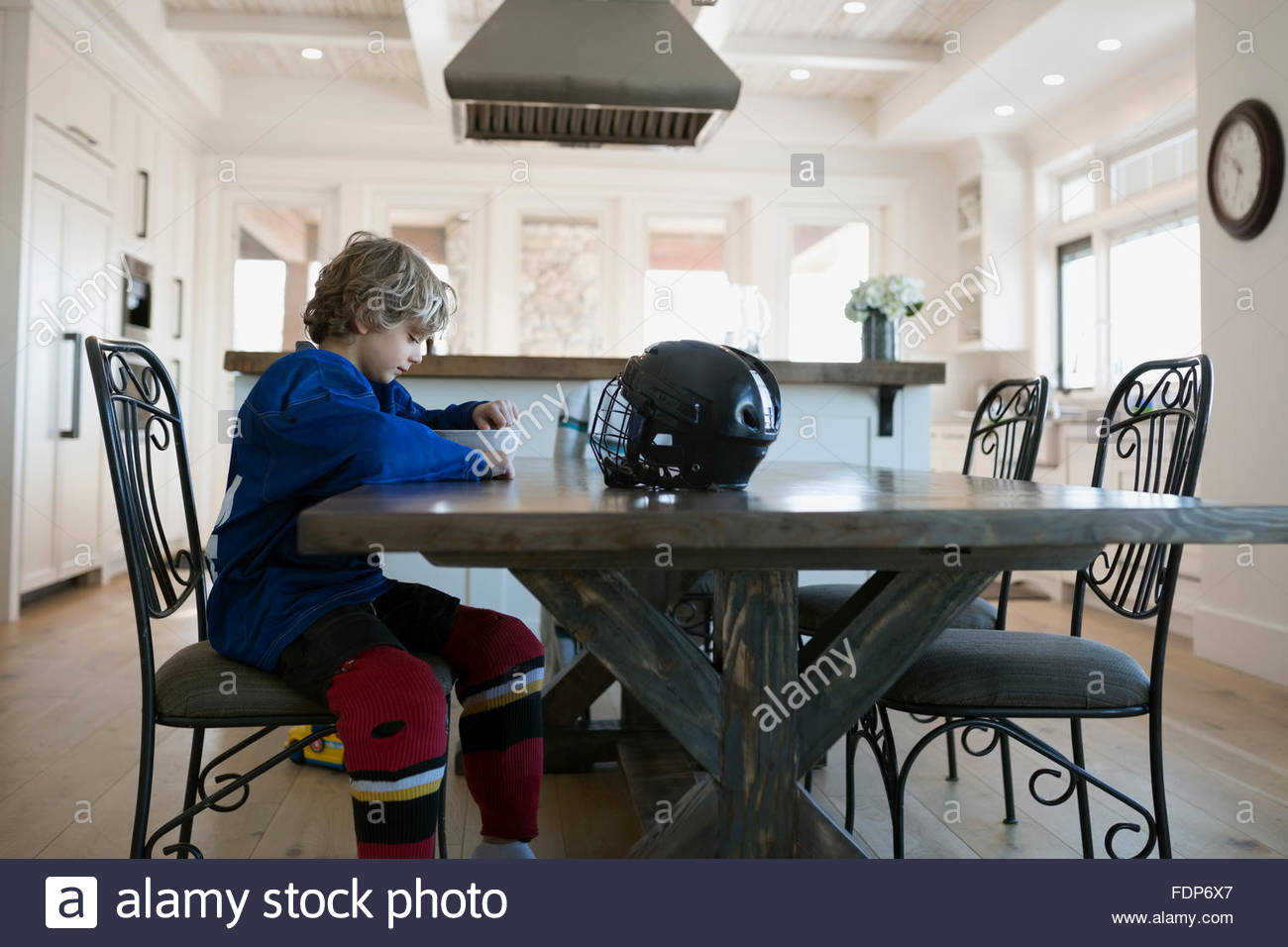 Boy in ice hockey uniform eating cereal table - Stock Image