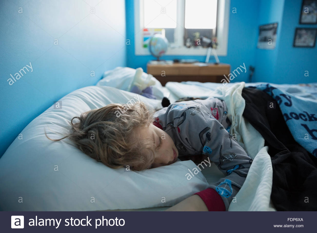 Boy sleeping in bed - Stock Image