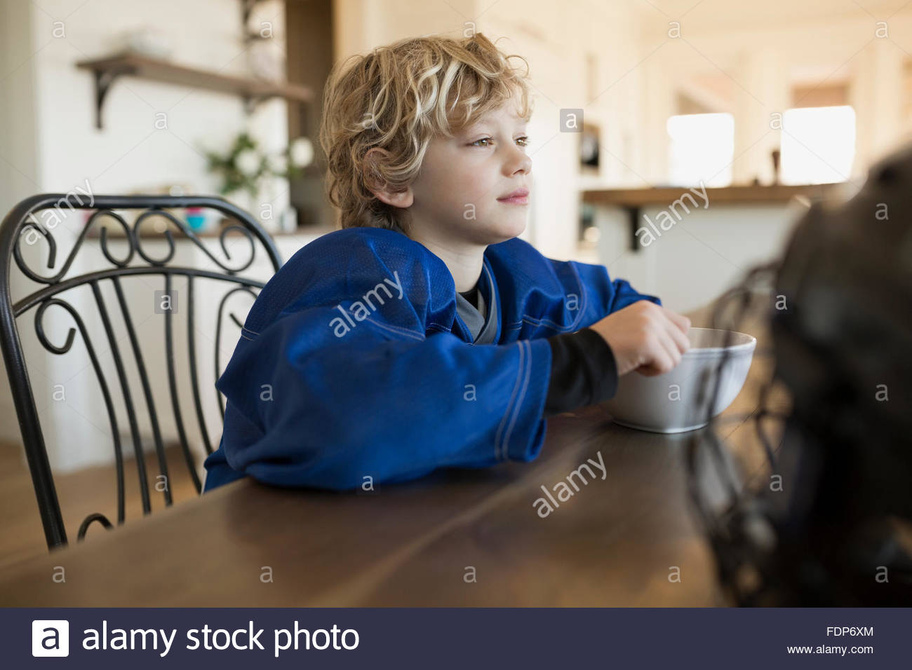 Pensive boy eating cereal at table - Stock Image