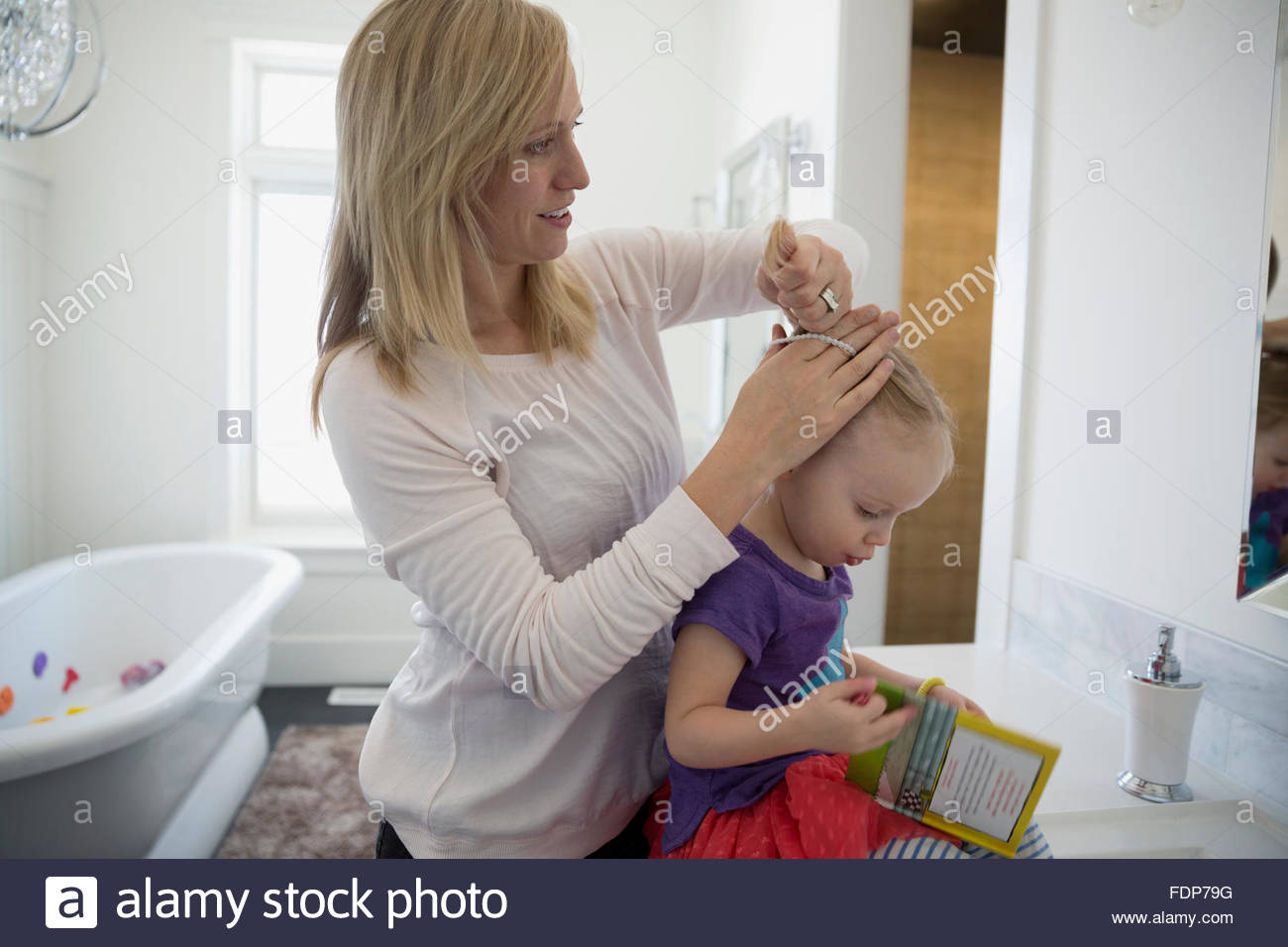 mother fixing daughters hair in bathroom - Stock Image