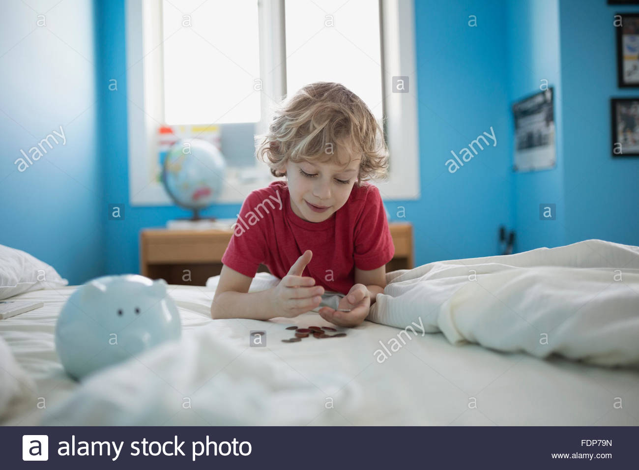 Boy counting piggy bank coins on bed - Stock Image