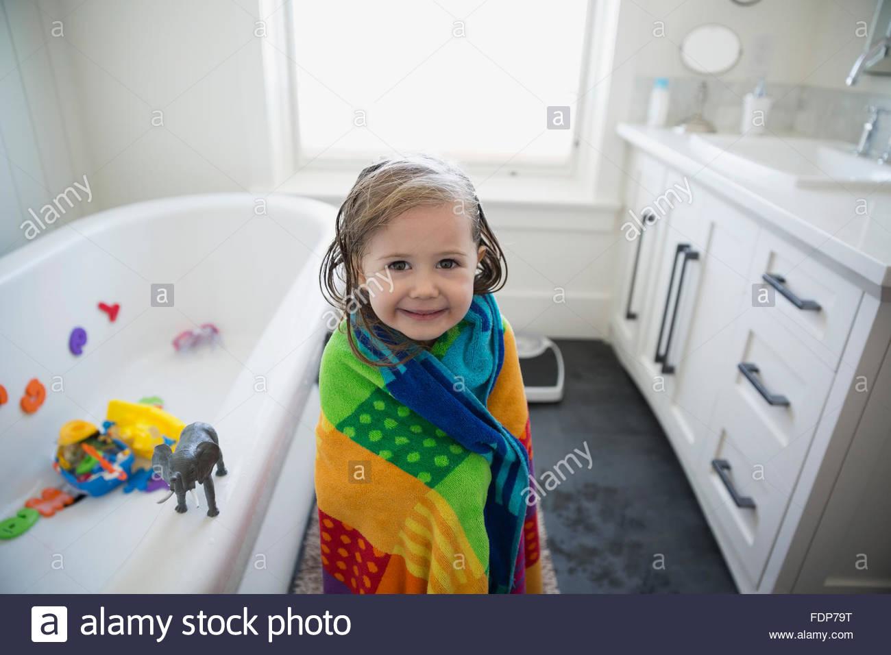 Portrait cute girl wrapped a towel bathroom - Stock Image