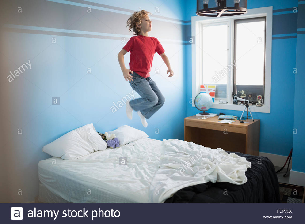 Boy jumping on bed - Stock Image