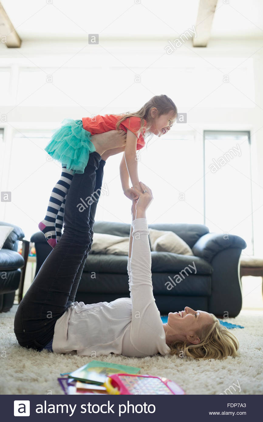 Mother lifting daughter with legs living room rug - Stock Image
