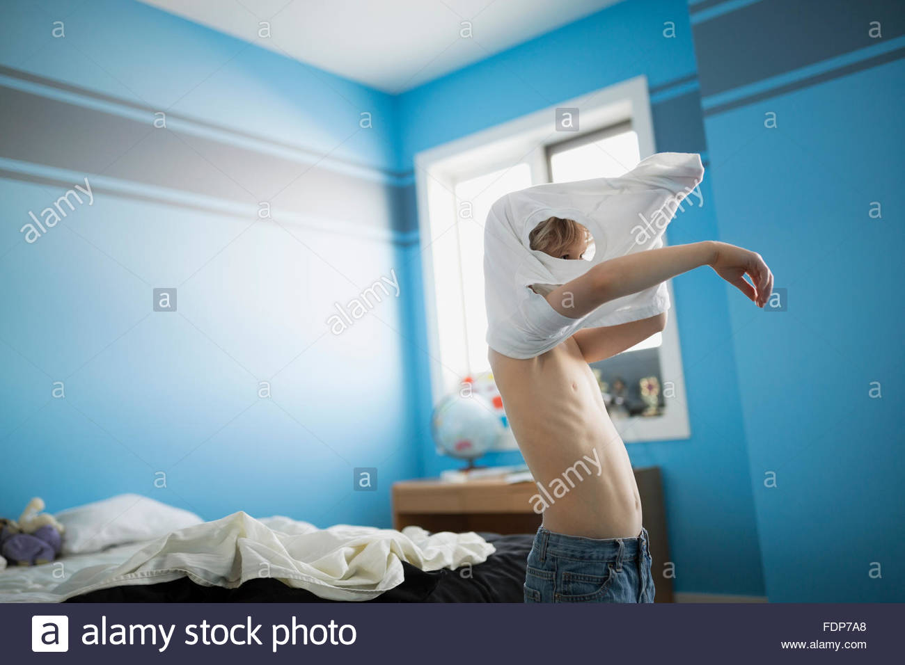 Boy putting on shirt in bedroom - Stock Image