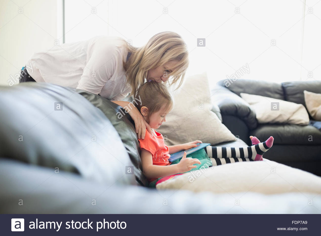 Mother watching daughter read book living room sofa - Stock Image