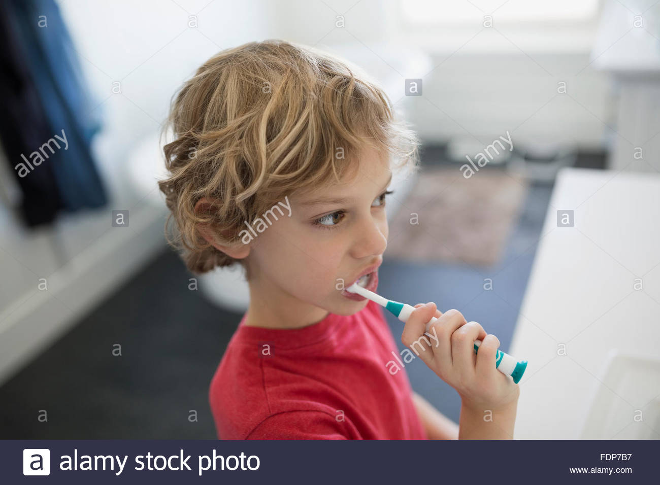 Boy brushing teeth in bathroom - Stock Image